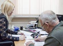 Een bejaarde die documenten ondertekenen Royalty-vrije Stock Foto's