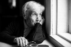 Een bejaarde die droevig uit het venster kijken Stock Afbeeldingen