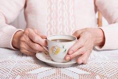 Een bejaarde drinkt thuis thee De hogere kop thee van de vrouwenholding in hun handen bij lijstclose-up royalty-vrije stock afbeelding
