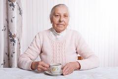 Een bejaarde drinkt thuis thee De hogere kop thee van de vrouwenholding in hun handen bij lijstclose-up stock afbeelding