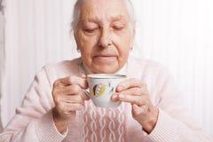 Een bejaarde drinkt thuis thee De hogere kop thee van de vrouwenholding in hun handen bij lijstclose-up royalty-vrije stock afbeeldingen