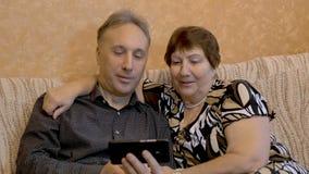 Een bejaarde en haar volwassen zoon letten op foto's van hun familie op een smartphone stock videobeelden