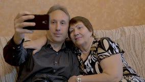 Een bejaarde en haar volwassen zoon worden gefotografeerd op een smartphone stock videobeelden