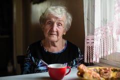 Een bejaarde gelukkige vrouw heeft thuis Ontbijtzitting royalty-vrije stock afbeeldingen