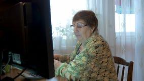 Een bejaarde, een grootmoeder, gebruikt een computer Het bestuderen van moderne technologieën stock footage