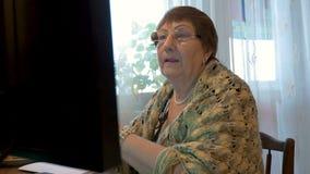 Een bejaarde, een grootmoeder, gebruikt een computer Het bestuderen van moderne technologieën stock video