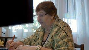 Een bejaarde, een grootmoeder, gebruikt een computer Het bestuderen van moderne technologieën Close-up stock videobeelden