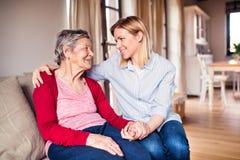 Een bejaarde grootmoeder met een volwassen kleindochter thuis royalty-vrije stock foto's