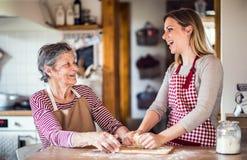 Een bejaarde grootmoeder met een volwassen kleindochter thuis, het bakken royalty-vrije stock foto