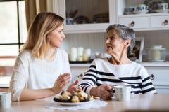 Een bejaarde grootmoeder met een volwassen kleindochterzitting bij de lijst die thuis, cakes eten royalty-vrije stock afbeeldingen