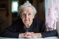 Een bejaarde in haar huis Stock Foto's