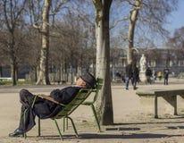 Een bejaarde in een hoed slaapt in de zon in het park royalty-vrije stock afbeeldingen