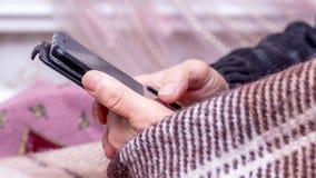 Een bejaarde houdt een smartphone in haar handen en zoekt de juiste informatie over Internet_ royalty-vrije stock foto's