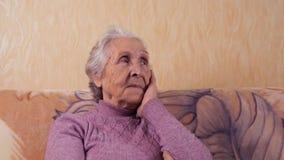 Een bejaarde kijkt weg Verouderde vrouw zorgvuldig het kijken weg stock videobeelden