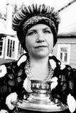 Een bejaarde kleedde zich in de oude Russische stijl met een samovar, een heldere headscarf op haar schouders en een bos van onge stock fotografie