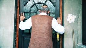 Een bejaarde klopt op de deur van zijn huis stock videobeelden