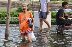 Een bejaarde is knie diep in water in een overstroomde straat van Bangkok, Thailand, op 31 Oktober 2011 stock fotografie