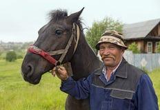 Een bejaarde landbouwer met zijn paard in de regen Oud-gelovigedorp Visim, Rusland Royalty-vrije Stock Foto's
