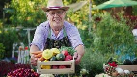 Een bejaarde landbouwer verkoopt groenten op de landbouwbedrijfmarkt stock video