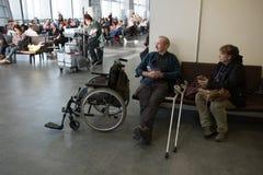 Een bejaarde met een beschadigd die been in een rolstoel door de luchthaven voor het inschepen wordt verstrekt royalty-vrije stock foto