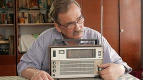 Een bejaarde met een snor zet uitstekende radio aan en luistert aan muziek Trekt de antenne terug, zet de knoop aan stock videobeelden