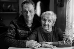 Een bejaarde met haar het volwassen kleinzoon stellen voor de camera royalty-vrije stock foto