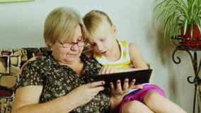 Een bejaarde met haar kleindochter die samen op een tablet spelen Heilige Communie van Generaties stock video