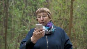 Een bejaarde mooie vrouw onderzoekt een smartphone en brengt schoonheid, kamt haar haar, aanpast haar kleren Voor een gang binnen stock footage