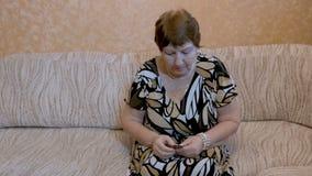 Een bejaarde neemt medicijn, zit thuis op de laag stock video