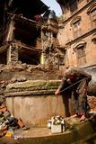 Een bejaarde Nepali-dame gebruikt een put onder aardbevingsruïnes i Stock Afbeeldingen