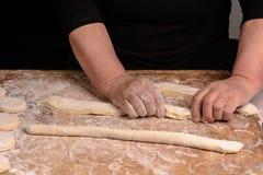 Een bejaarde ontwikkelt van een ruw beslag voor baksel op een donkere achtergrond stock fotografie