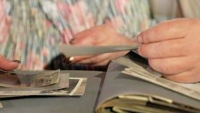 Een bejaarde paarman en een vrouw bekijken hun oude foto's van het huis Close-up van handen stock footage