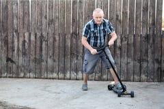Een bejaarde probeert om een autoped te drijven om zijn zonen te onderwijzen Stock Afbeeldingen