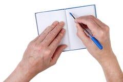 Een bejaarde schrijft adressen van vrienden in een document notitieboekje stock foto