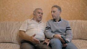 Een bejaarde spreekt met zijn zoon stock video
