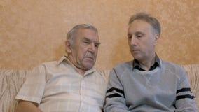 Een bejaarde spreekt met zijn zoon Zij zitten op de laag stock video