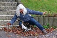 Een bejaarde struikelt over een kat stock foto's