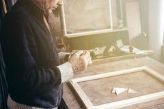 Een bejaarde timmerman werkt in zijn workshop stock fotografie