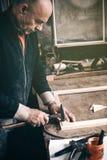 Een bejaarde timmerman werkt in zijn workshop stock afbeeldingen