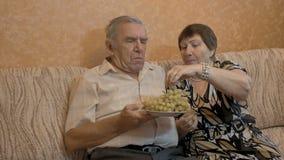 Een bejaarde voedt haar echtgenoot` s druiven Zij zijn een gelukkig paar stock footage