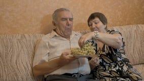 Een bejaarde voedt haar echtgenoot` s druiven Zij zijn een gelukkig paar stock video