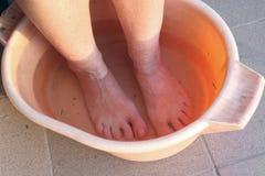 Een bejaarde vrouw die van het land haar vuile voeten in een oranje pla wassen stock afbeeldingen