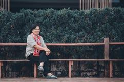 Een bejaarde zit in een openbaar park stock foto's