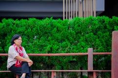 Een bejaarde zit in een openbaar park stock foto