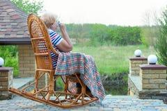 Een bejaarde zit in een rieten schommelstoel en en drinkt een kop van hete thee Ontspan in een buitenhuis Stock Foto