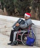 Een bejaarde zit in een rolstoel en speelt de harmonika in de oude stad van Nazareth in Israël royalty-vrije stock foto