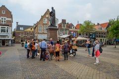Een belemmeringenverkoper, door toeristen op het grote stadsvierkant wordt omringd, I die royalty-vrije stock foto