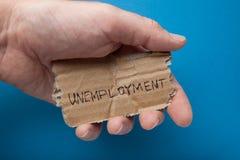 Een bericht op een oud gescheurd karton in zijn hand, close-up werkloosheid royalty-vrije stock afbeelding