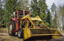 Een beschadigde gele die tractor in een kustlijn van een meer door pijnboomboom wordt omringd in een mooie vreedzame de zomerdag stock foto's