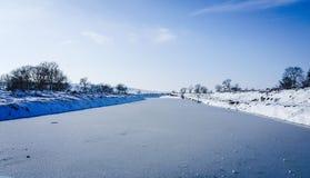 Een bevroren rivier in gevangenschap dichtbij de koude Sneeuw en blauwe hemel met wolken en stok Ik houd van op een bevroren rivi royalty-vrije stock fotografie